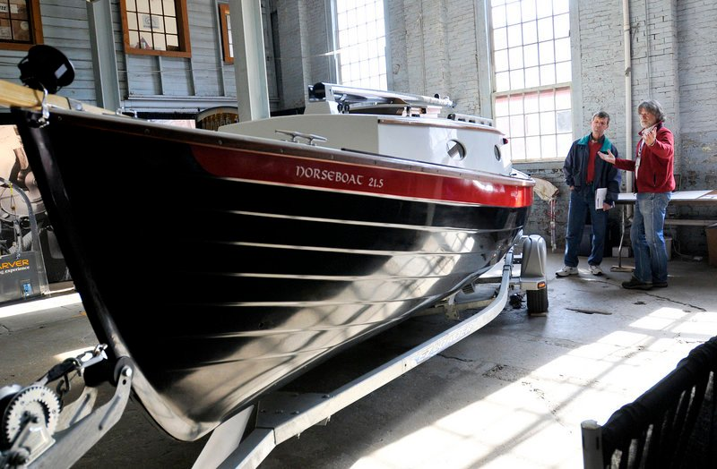 Kevin Jeffrey, right, shows off a NorseBoat 21.5 Sunday to Rich Kania of Brunswick during the Maine Boatbuilders Show at the Portland Company Complex on Sunday. Exhibitors reported a definite uptick in business at the show after several years of slow sales.