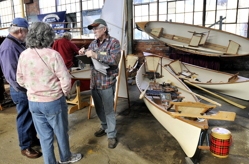 Steve Kaulback, founder of Adirondack Guideboat Inc. out of Charlotte, Vt., talks with visitors at the Maine Boatbuilders Show.