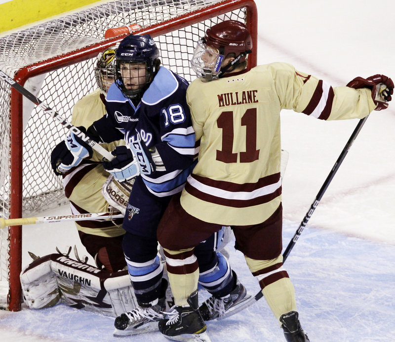 Jon Swavely of Maine is sandwiched between Boston College goaltender Parker Milner, left, and Pat Mullane in the first period of the Hockey East final Saturday.