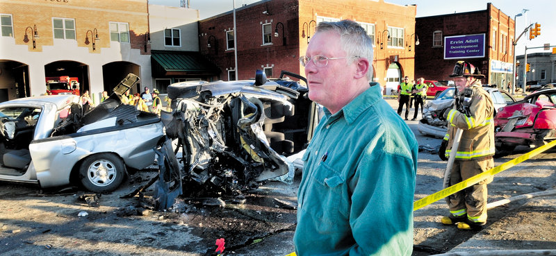 Bob Woodsome of Fairfield talks about the six-vehicle crash that occurred when the Suzuki, behind him, slammed into vehicles at a traffic light at College Avenue and Main Street in Waterville on Sunday. A truck at left and two cars at right were struck. Waterville firefighter Marshal King monitors the scene.
