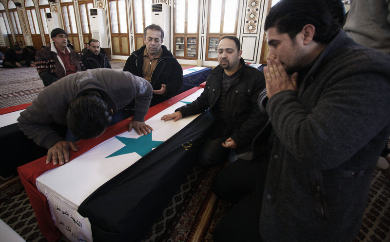 Mourners attend a funeral on Sunday for a victim of a suicide bomb attack in Damascus, Syria.