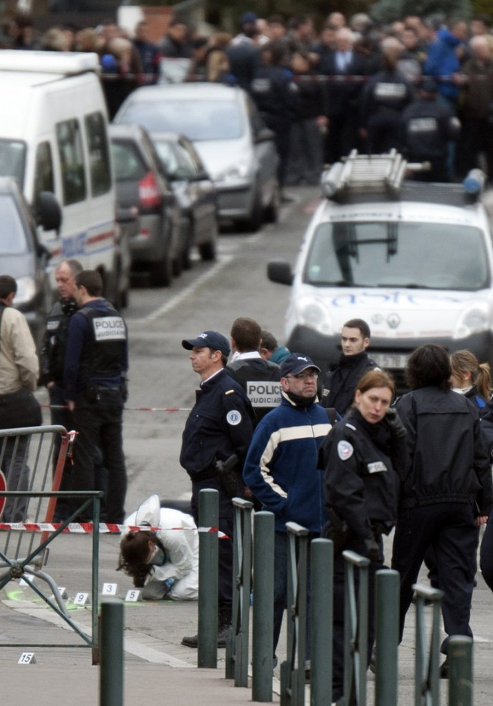 Police officers gather at the site of a shooting in Toulouse, southwestern France, Monday. Fourteen new units of riot police and gendarmes have been added to the region.