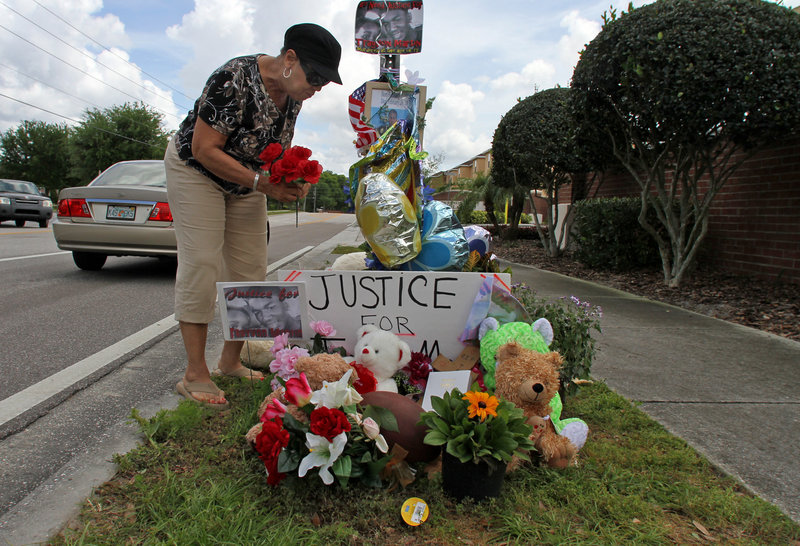 Claudette Hutchinson of Sanford adds to a memorial Tuesday for teenager Trayvon Martin outside the Retreat at Twin Lakes, where Trayvon was shot and killed.