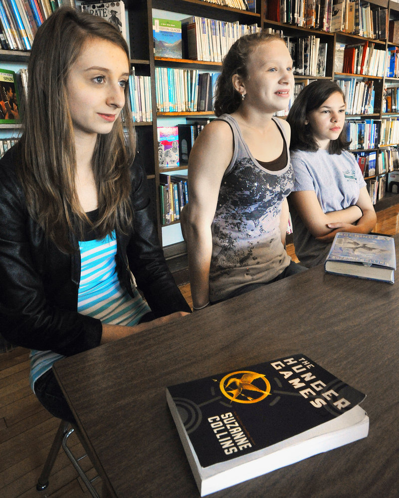 "Edita Isakovic, Madison Houlette and Maggie Koukos, eighth-graders at South Portland's Mahoney Middle School, discuss the popular novel ""The Hunger Games."" About 120 Mahoney students will take a field trip to see the movie on Friday."