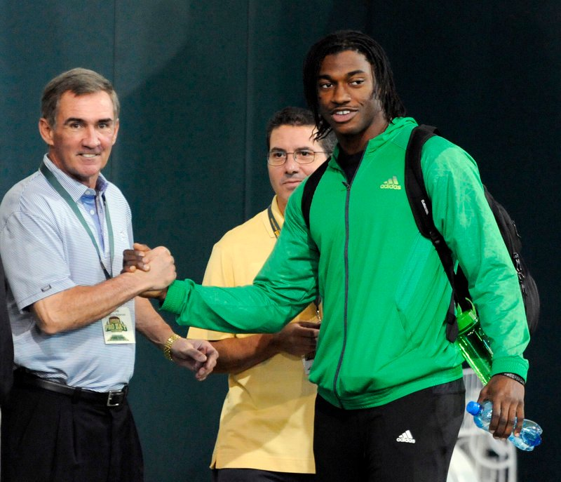 Redskins Coach Mike Shanahan shakes hands with Heisman winner Robert Griffin III during Baylor's NFL pro day Wednesday. The Redskins expect to draft Griffin next month.