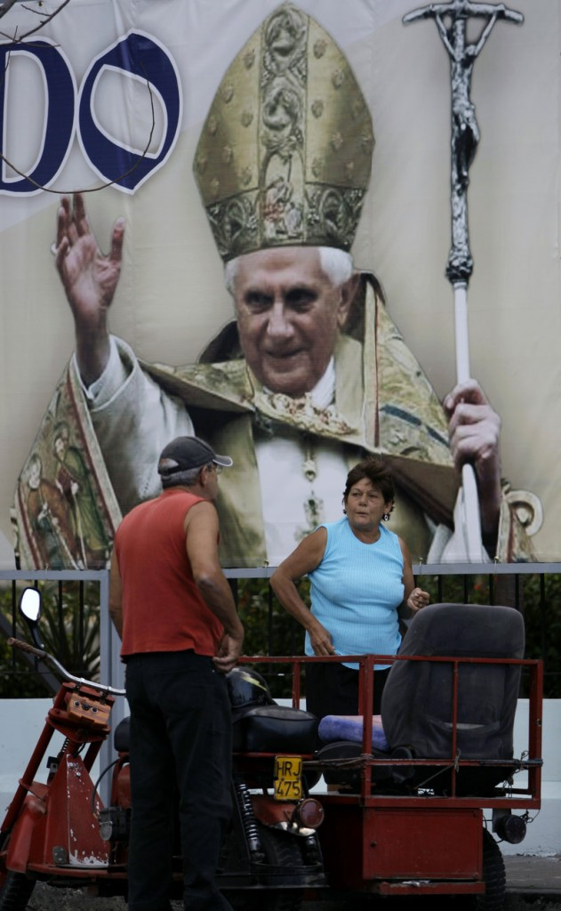 A couple speaks in the street where an image of Pope Benedict XVI hangs in Havana, Cuba, on Thursday. The pope is visiting Mexico and heads for Cuba on Monday.