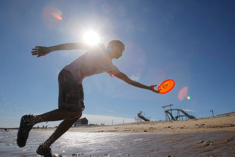Matthew Laforest of Old Orchard Beach reaches to catch a frisbee while throwing it at Old Orchard Beach with his friend Josh Baumann during Friday's warm and breezy weather.