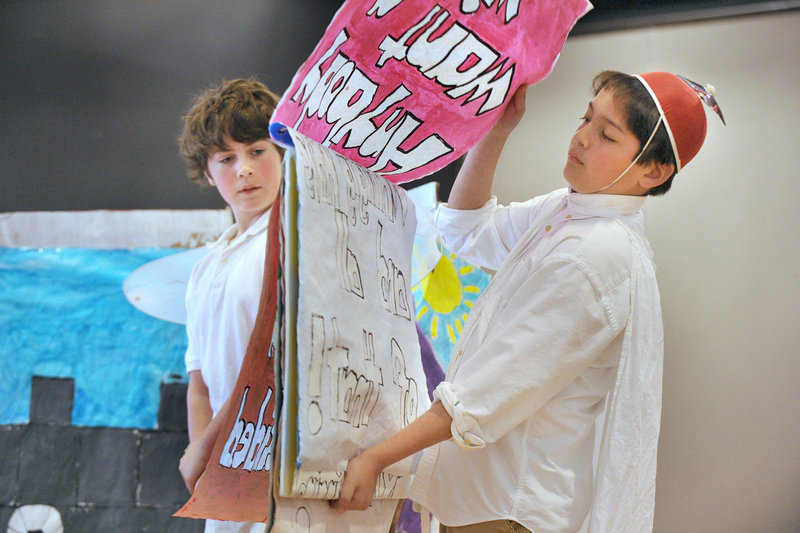"Ethan Carmolli changes his sign during his non-speaking role in the Edgecomb Eddy School's team performance in the ""Odyssey Angels"" competition Saturday in Wells."
