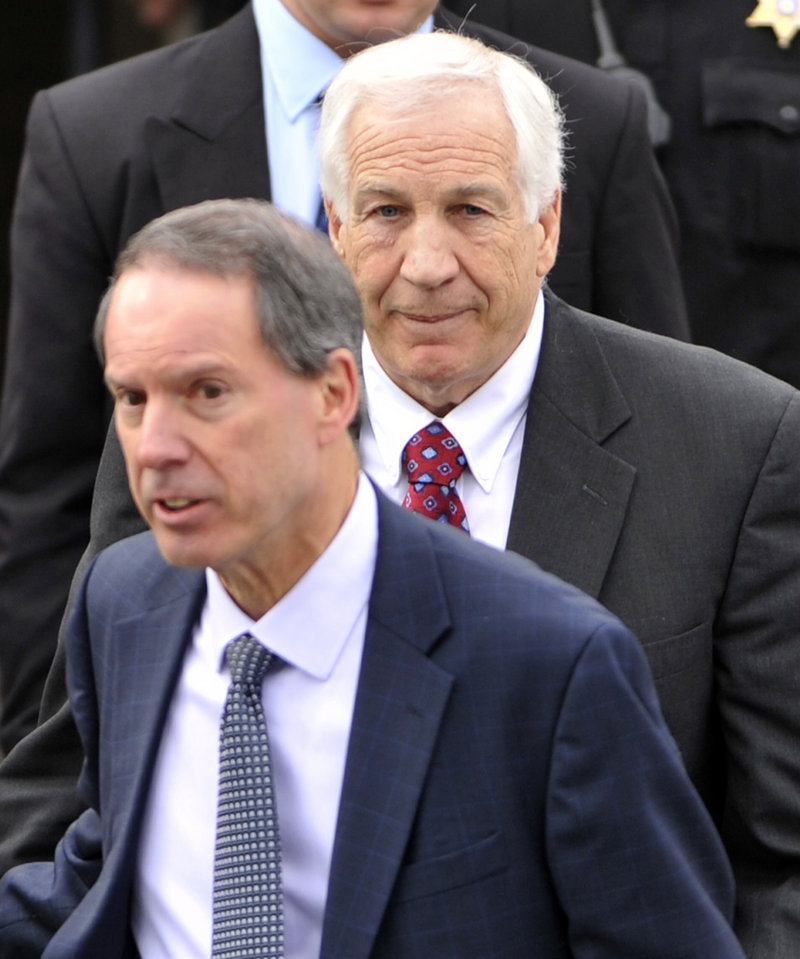 Jerry Sandusky, back, a former Penn State assistant football coach charged with sexually abusing boys, and his attorney, Joseph Amendola, front, leave the Centre County Courthouse, in Bellefonte, Pa., after a hearing in February.