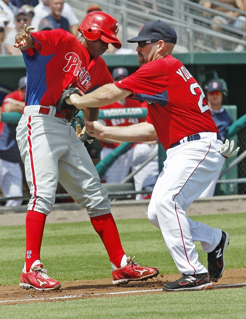 Kevin Youkilis of the Boston Red Sox tags out Juan Pierre of the Philadelphia Phillies to end a rundown Saturday during the Phillies' 10-5 victory at Fort Myers, Fla. Also Saturday, the Red Sox beat the Miami Marlins, 4-1.