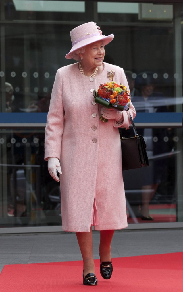 Britain's Queen Elizabeth II dropped in on a couple's wedding while visiting Manchester Town Hall on Friday.