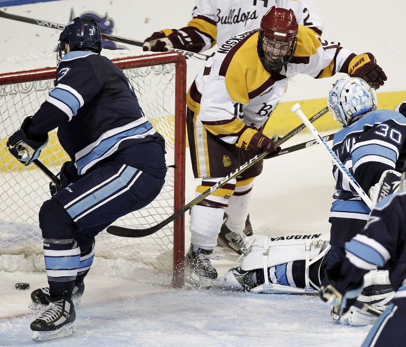 Jake Hendrickson stuffs the puck in the goal past Maine defenseman Mark Nemec and goaltender Dan Sullivan, giving the Bulldogs a 3-2 lead in the second period.