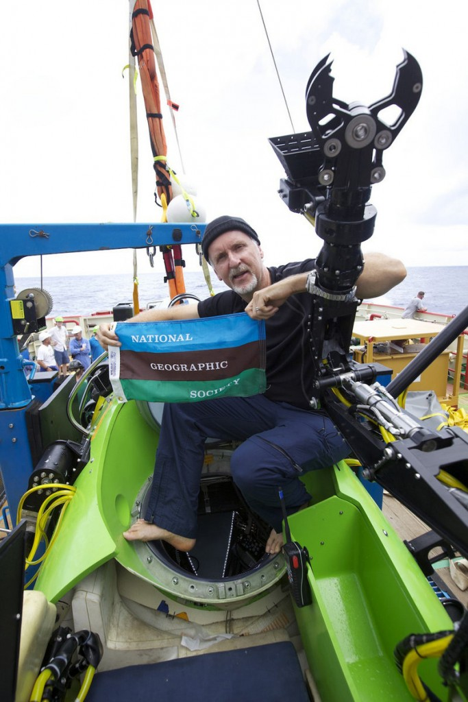 James Cameron holds the National Geographic Society flag after he successfully completed a solo dive to the Mariana Trench. National Geographic was one sponsor of the expedition. Cameron said his super-strong sub shrank three inches under the intense water pressure.