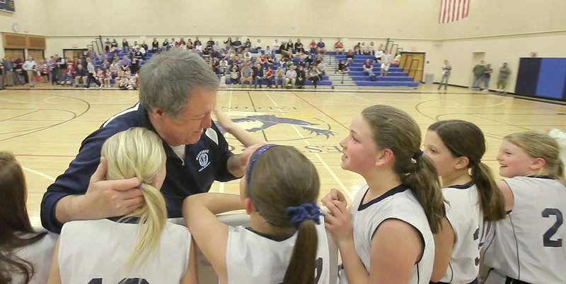 Lou Lampron hugs his players after being honored for his tireless work over 20 years in organizing and running a middle-school basketball tournament in Westbrook.