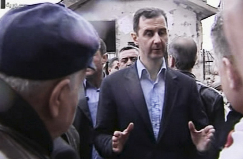In an image made from video, Syrian President Bashar Assad visits the Baba Amr neighborhood, a former rebel stronghold in Homs, on Tuesday. Government forces now control Homs.