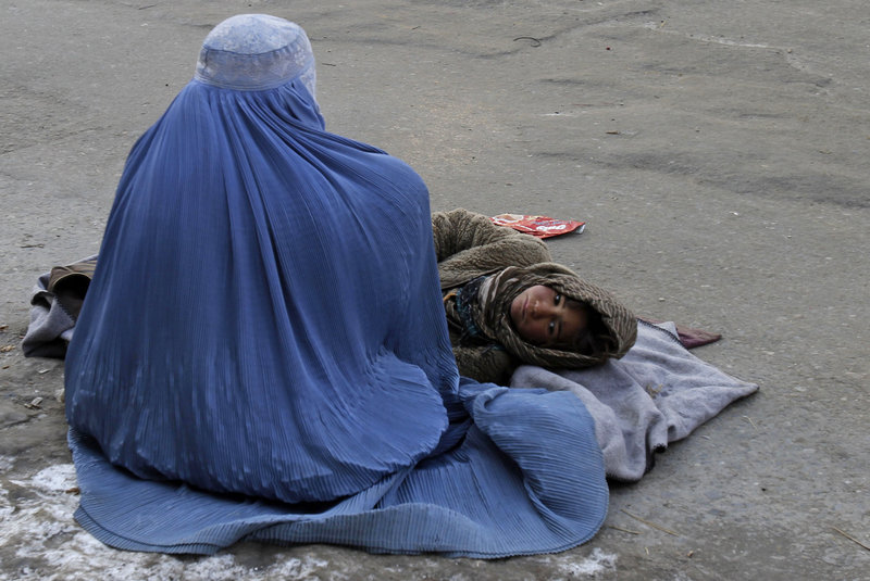 An Afghan woman begs with her child in Kabul. Human Rights Watch reports that Afghan women can be imprisoned for being raped or escaping domestic abuse.
