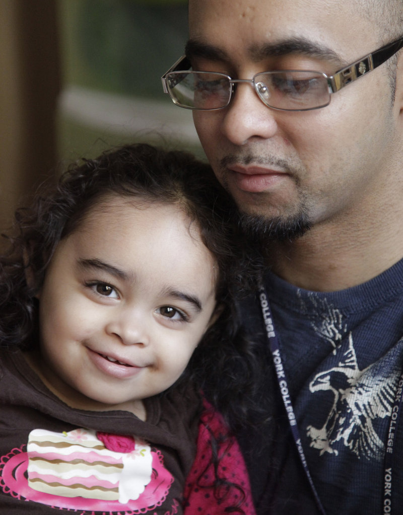 Cristina Astacio, 2, recently diagnosed with a mild form of autism, listens as her dad, Christopher Astacio, reads to her. Autism cases are reported on the rise again.
