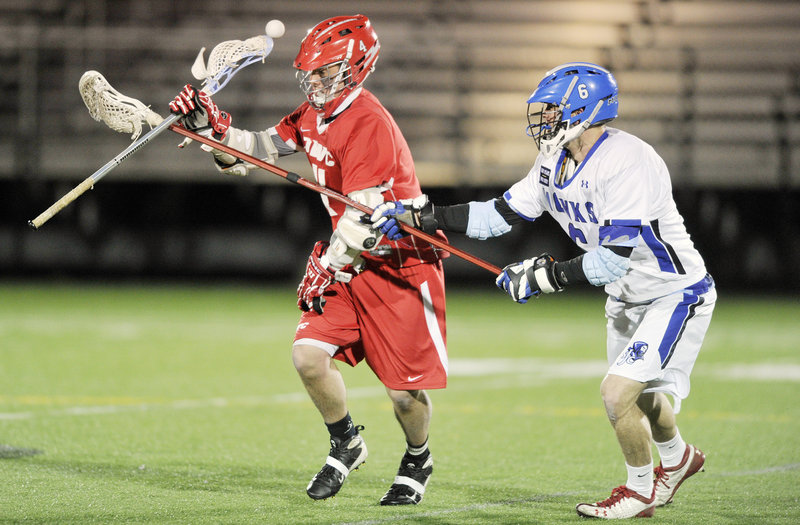 Bob Murtha of St. Joseph's College, right, knocks the ball loose from a Daniel Webster player in the first quarter of their men's lacrosse game Thursday night at Deering High. St. Joseph's came away with a 13-5 victory.