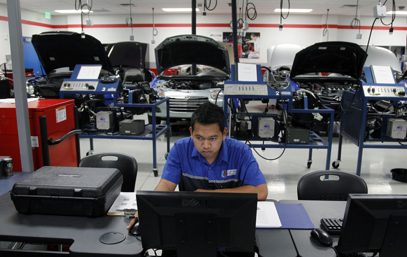 At the Universal Technical Institute in Irving, Texas, student Phalla Keo does research in his mechanic class. The industry is churning out technicians at the same time that warranty repairs are down and maintenance work is declining.