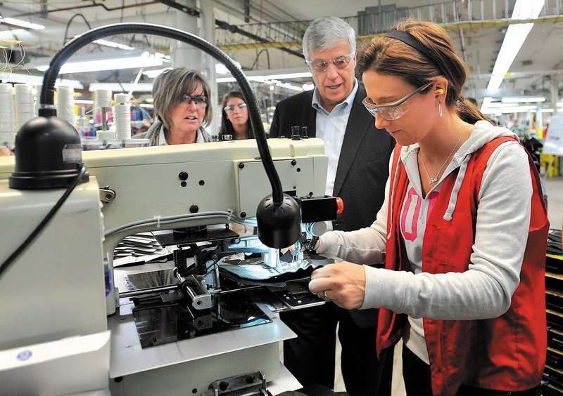 Rep. Mike Michaud, center, speaks with New Balance factory employee Tiffany Whitney on Friday morning in Norridgewock, where he toured the plant and picked up a pair of running shoes made for President Obama.