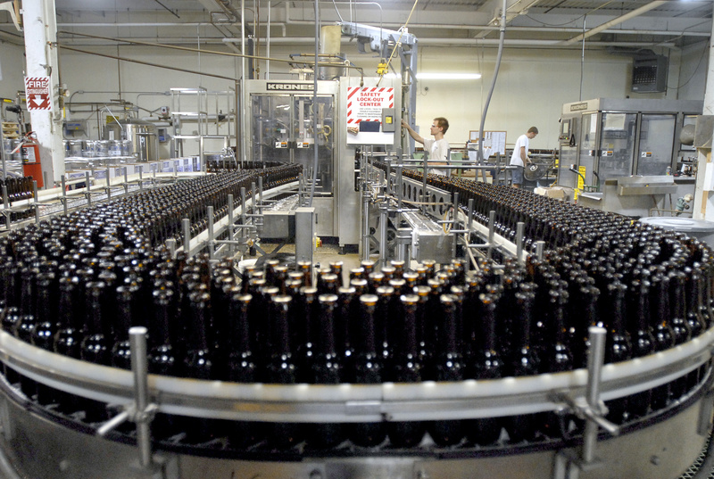 Empty bottles fill a conveyor belt at the Shipyard Brewing Co. in Portland. From 1996 to 2011, the city and the Portland Water District failed to bill the brewery for most of its sewer services, an error that cost the city as much as $1.5 million in lost revenue.