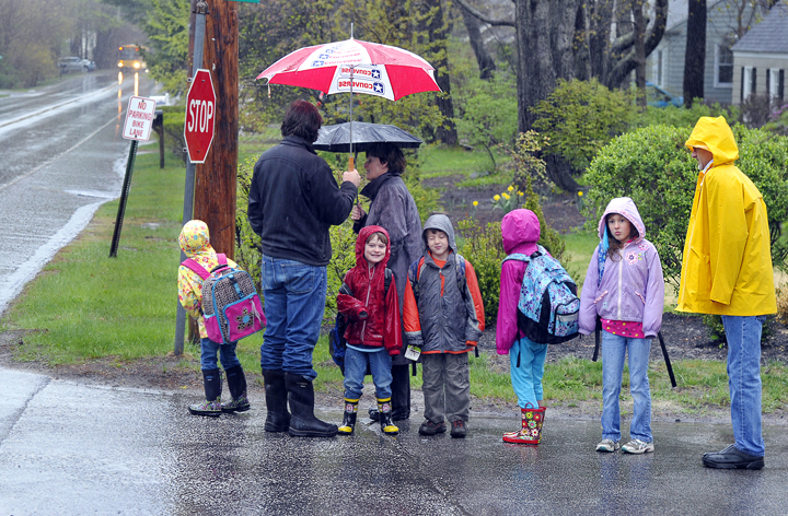 Three Mussel Cove families wait for the school bus in Falmouth as the rain falls heavily. The bus was about 15 minutes late and they were getting anxious. From left are parents Graham Haynes, Mary Smith and Mark Woodbury waiting with their children, who attend kindergarten through the third grade.