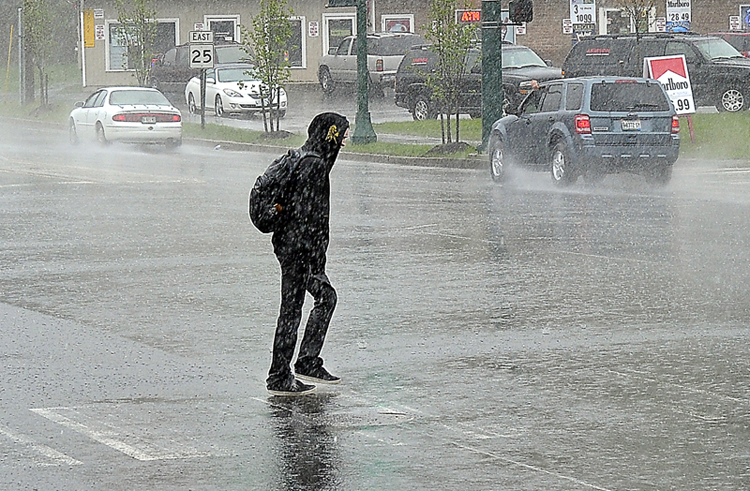 A pedestrian takes it in stride as a heavy downpour at the intersection of Stroudwater and Wayside Drive doesn't deter his casual walk across the Westbrook bypass.