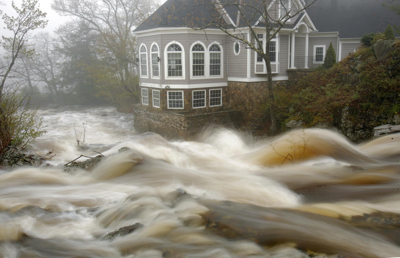 The Ogunquit River, swollen from Monday's rain, flows past a home in Ogunquit. Parts of southern Maine got more than 4 inches of rain.