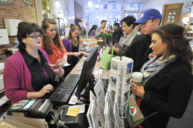 """A """"cash-mob"""" swarms Lisa-Marie's Made in Maine on Exchange Street in Portland on Thursday evening. Shop owner Lisa-Marie Stewart, left, rings up a sale."""