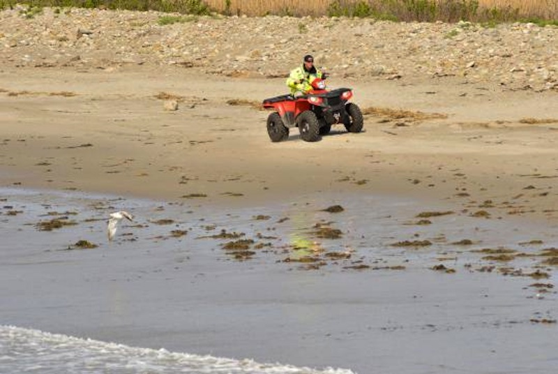 A police officer rides on the closed Rockport beach as part of the search for missing 2-year-old Caleigh Anne Harrison.
