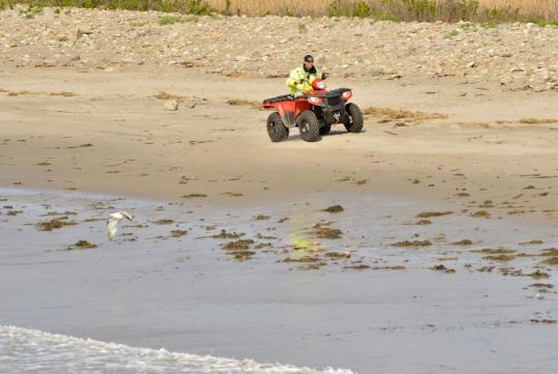 A police officer rides on the closed Rockport beach Friday as part of the search for missing 2-year-old Caleigh Anne Harrison.