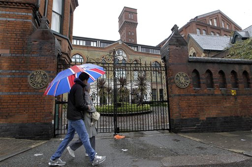 People walk past gated residential flats in Bow, east London, where the Ministry of Defence has warned residents that surface-to-air missiles could be positioned on their rooftops during the London Olympics.