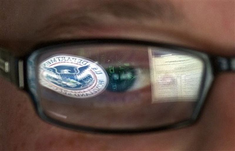 This Sept. 30, 2011 file photo shows a reflection of the Department of Homeland Security logo in the eyeglasses of a cybersecurity analyst at the watch and warning center of the Department of Homeland Security's secretive cyber defense facility in Idaho Falls, Idaho. The center is tasked with protecting the nation's power, water and chemical plants, electrical grid and other facilities from cyber attacks. (AP Photo/Mark J. Terrill, File)