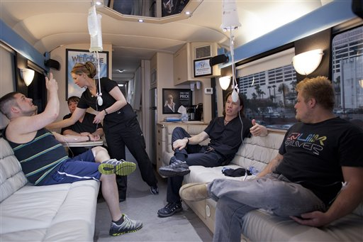 Bryan Dalia, left, of Caldwell, N.J. makes a photo of his IV bag while being treated on the Hangover Heaven bus by EMT Stacey Kreitlow, second from left, and Dr. Jason Burke, second from right, as another patient named Alex, right, looks on.