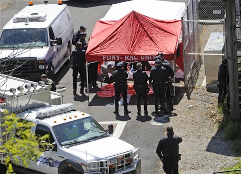 Police surround a temporarily built tent where the victims of the vehicle crash were brought, Sunday April 29, 2012, in New York. Authorities say the out-of-control van plunged off a roadway near the Bronx Zoo, killing seven people, including three children. (AP Photo/ Louis Lanzano)
