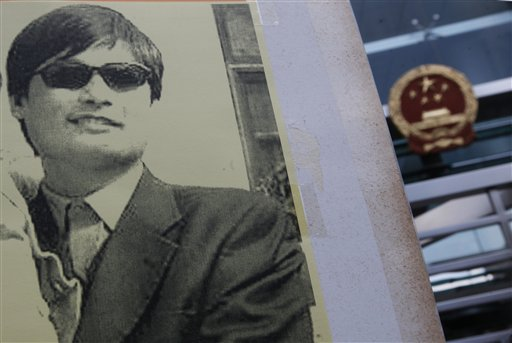 A pro-democracy protester holds a placard with picture of blind Chinese legal activist Chen Guangcheng outside China's Liaison Office in Hong Kong today.