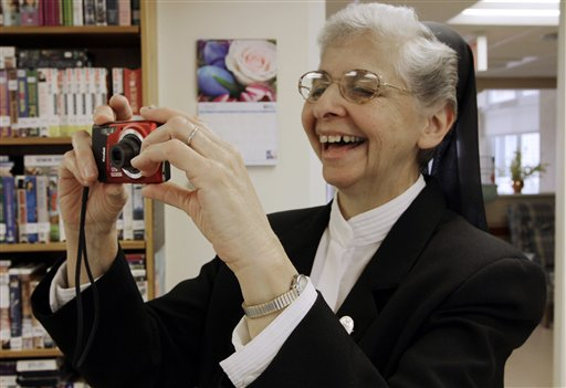 In this April 10, 2012 photo, sister Elaine Lachance takes a photo at the St. Joseph Convent in Biddeford, Maine. Good Shepherd Sisters of Quebec has just five convents in Maine and Massachusetts with fewer than 60 sisters. The youngest is 64, and it's been more than 20 years since a new member has joined. Sister Lachance is using the Internet, social media and even a blog to attract women who feel the calling to serve God. (AP Photo/Pat Wellenbach)