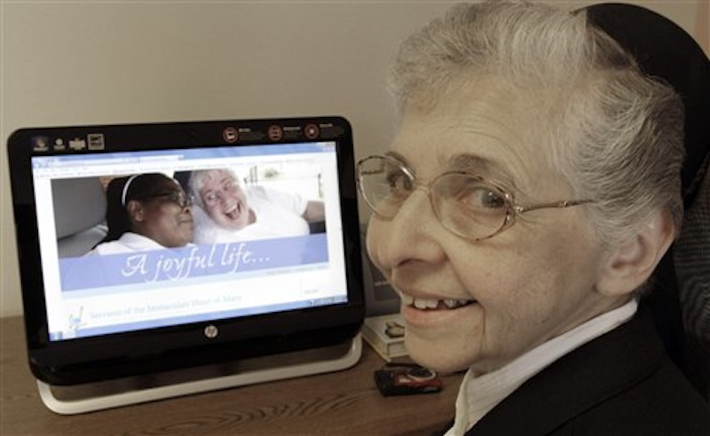 In this April 10, 2012 photo, sister Elaine Lachance works at a computer displaying a photo from the St. Joseph convent on it, in Biddeford, Maine. Good Shepherd Sisters of Quebec has just five convents in Maine and Massachusetts with fewer than 60 sisters. The youngest is 64, and itís been more than 20 years since a new member has joined. Sister Lachance is using the Internet, social media and even a blog to attract women who feel the calling to serve God. (AP Photo/Pat Wellenbach)