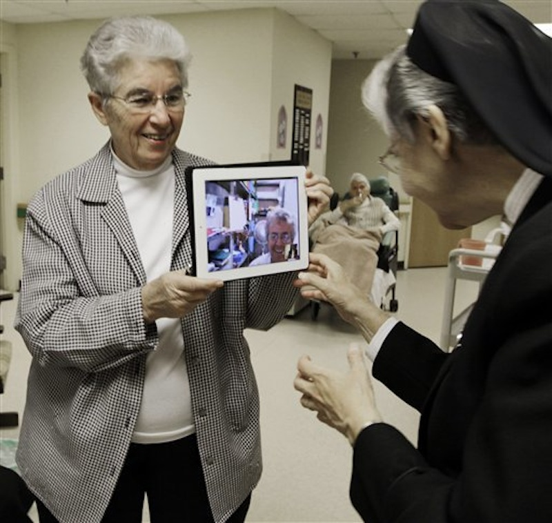 In this April 10, 2012 photo, sister Priscille Roy, left, holds up an iPad displaying her colleague, Sister Pauline Demers, who is in Brazil, to show Sister Elaine Lachance, right, at St. Joseph Convent in Biddeford, Maine. Good Shepherd Sisters of Quebec has just five convents in Maine and Massachusetts with fewer than 60 sisters. The youngest is 64, and itís been more than 20 years since a new member has joined. Sister Lachance is using the Internet, social media and even a blog to attract women who feel the calling to serve God. (AP Photo/Pat Wellenbach)