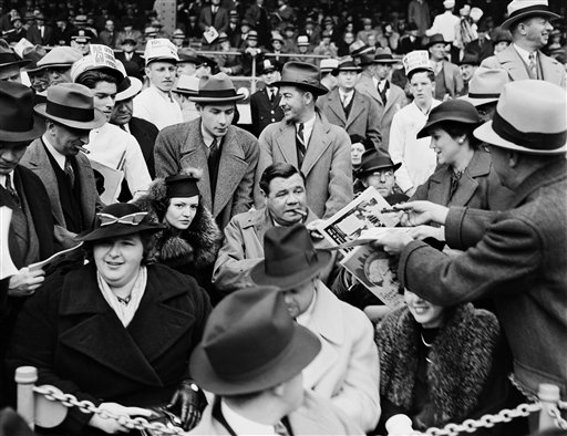 A man hands a program to baseball legend Babe Ruth, center, as he is joined by his second wife Clare, center left, and singer Kate Smith, front left, in the grandstand during Game 1 of the 1936 World Series at the Polo Grounds in New York. The photo is one of those posted online by the New York City Municipal Archives.