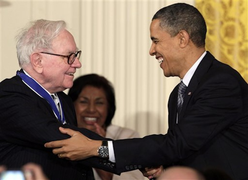 In this Feb. 15, 2010, file photo President Barack Obama congratulates Warren Buffett after presenting him with a 2010 Presidential Medal of Freedom in an East Room ceremony at the White House in Washington. In his weekly radio and internet address Saturday April 14, 2012, Obama urged Americans to ask their member of Congress to support the
