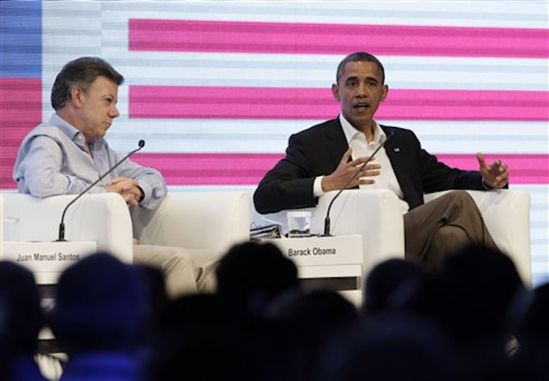 Colombia's President Juan Manuel Santos, left, sits next to President Barack Obama who speaks to an audience gathered at the CEO Summit of the Americas, in Cartagena, Colombia, Saturday April 14, 2012. Regional business leaders are meeting parallel to the sixth Summit of the Americas which brings together presidents and prime ministers from Canada, the Caribbean, Latin America and the U.S. (AP Photo/Carolyn Kaster)