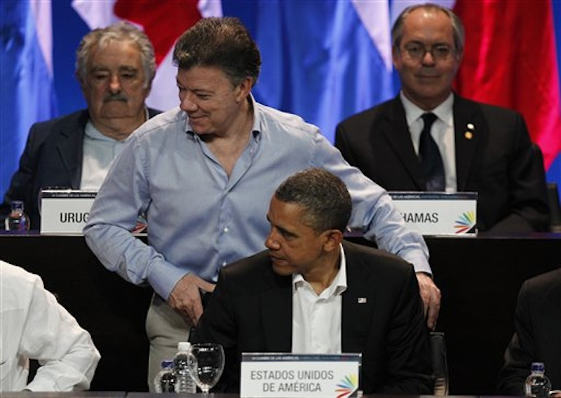 Colombia's President Juan Manuel Santos stands behind President Barack Obama at the opening ceremony of the sixth Summit of the Americas at the Convention Center in Cartagena, Colombia, Saturday April 14, 2012. The summit brings together presidents and prime ministers from Canada, the Caribbean, Latin America and the U.S. Back left is Uruguay's President Jose Mujica. (AP Photo/Fernando Vergara)