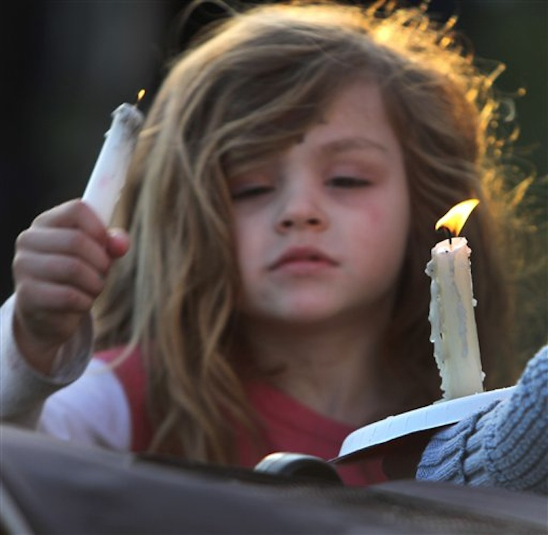Addie Delisle lights her candle during a vigil for slain Police chief Michael Maloney, Friday, April 13, 2012 in Greenland, N.H. Maloney was trying to serve a search warrant Thursday night when a suspect opened fire, killing the 48-year-old chief, injuring four officers from other departments, and plunging the southeastern New Hampshire community of Greenland into a grief that residents say they won't soon get over. (AP Photo/Jim Cole)