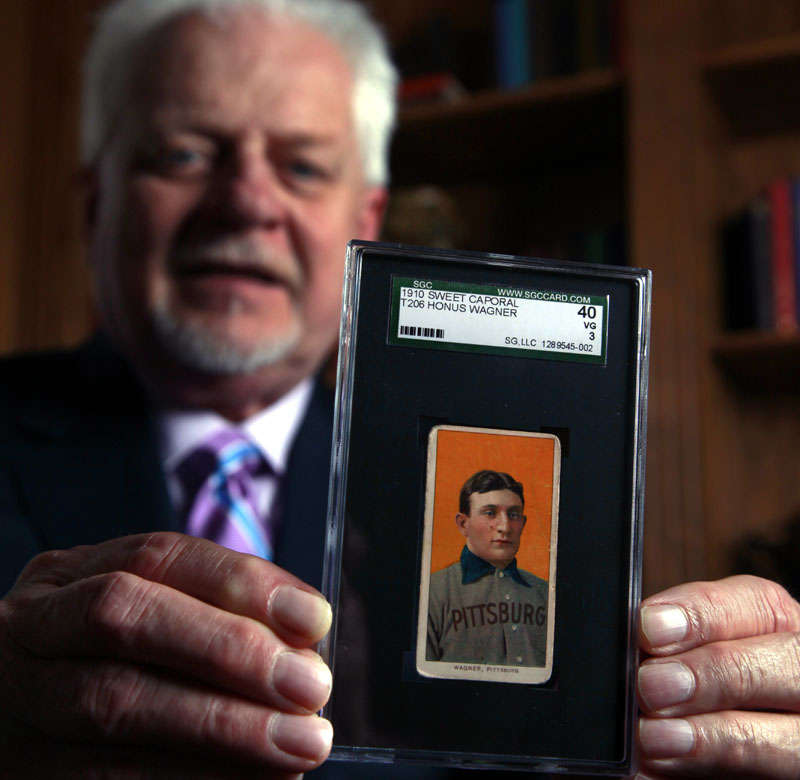 Bill Goodwin holds a 1909 Honus Wagner baseball card last month in Sunset Hills, Mo. Goodwin facilitated an online auction for the card, one of the most sought-after sports collectibles in the world.