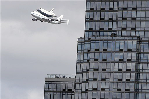 People watch from the balcony of a building as the space shuttle Enterprise, riding on the back of the NASA 747 Shuttle Carrier Aircraft, cruises over the Hudson River today.