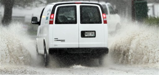 A vehicle navigates through a flooded street in Brunswick today as the state received its first major rain storm during April.