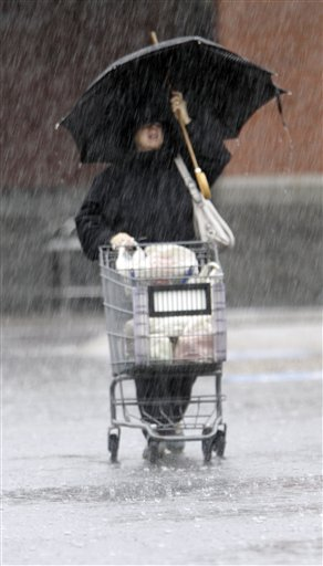 A shopper braves heavy rain while leaving a grocery store in Brunswick today.