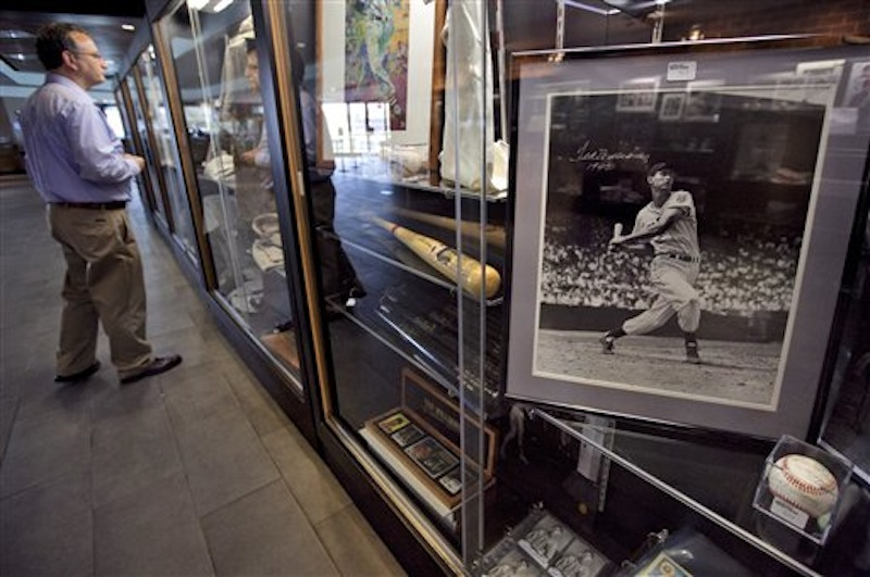 Baseball fan Sumner Friedstein, of West Newbury, Mass., left, views items once owned by Boston Red Sox's Ted Williams near a photograph of Williams from the 1942 season, right, in a display case at Fenway Park during an auction preview, Wednesday, April 25, 2012, in Boston. (AP Photo/Steven Senne)