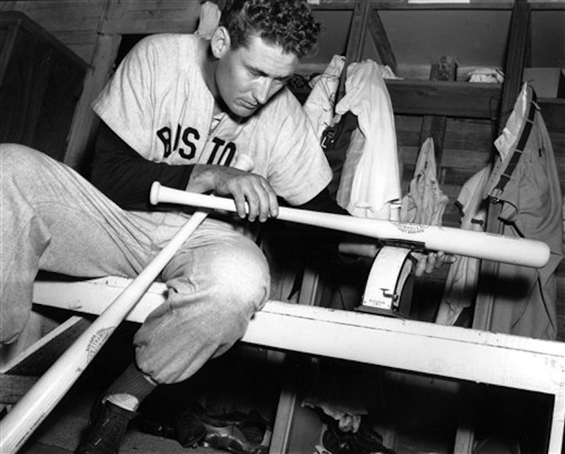 In this March 16, 1948 file photo, Boston Red Sox Ted Williams weighs one of his new 36-ounce Hickory baseball bats in the clubhouse after morning workout at spring training in Sarasota, Fla. (AP Photo)